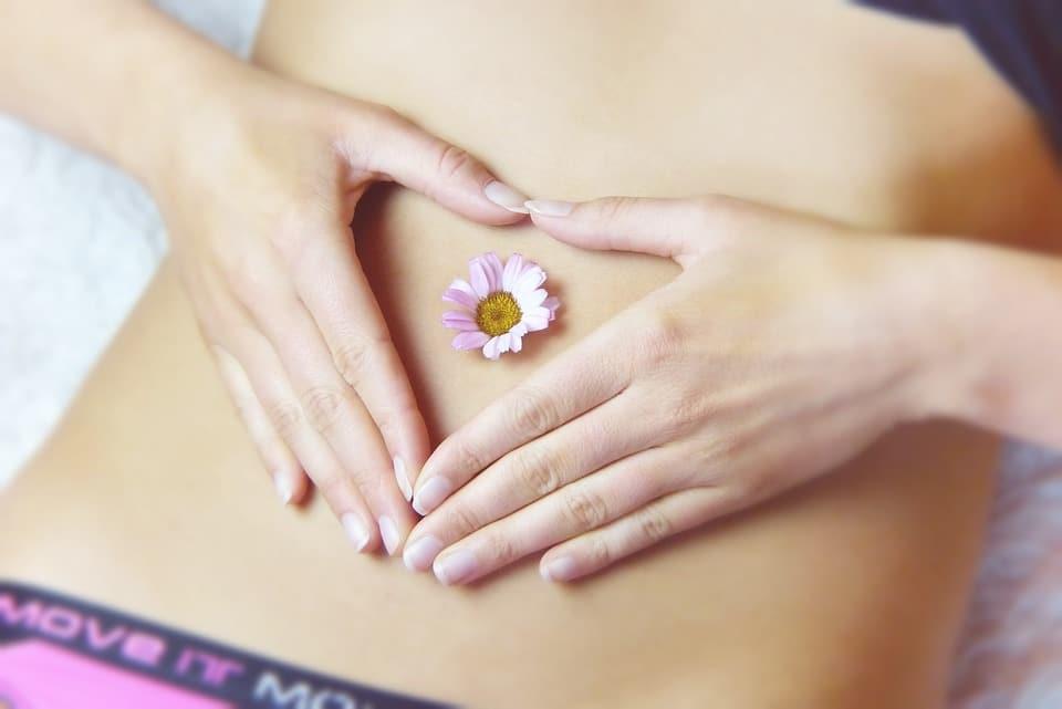Femme qui met ses mains en coeur sur son ventre avec une fleur dans le nombril