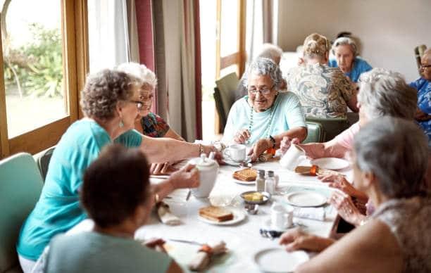 Groupe de personnes âgées qui prennent leur repas en maison de retraite
